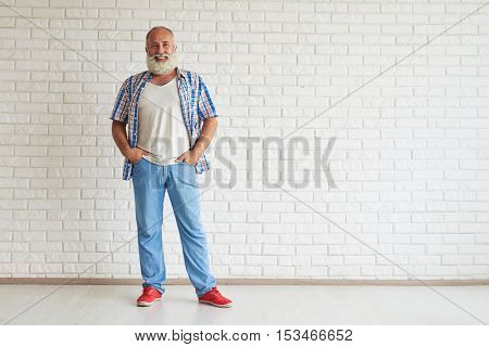 Smiling senior dressed fashionably standing and holding hands in his pockets, white brick wall on background