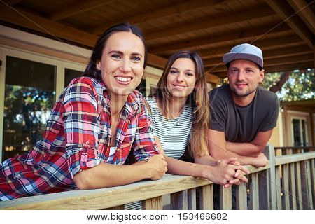 Mid side view shot of delighted smiling friends who are posing together at the camera. With a background of modern resting house behind them. Spending summer vacation together