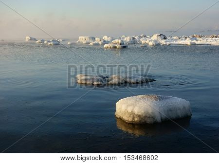 Winter scene with snow covered rocks by the Baltic sea in Helsinki, Finland on cold winter morning with sea smoke in Helsinki, Finland on 6 January 2016