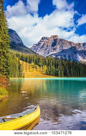 In shallow water, the boat is moored. The concept of eco-tourism and active tourism. The mountain Emerald lake.  Sunny day in autumn Yoho National Park
