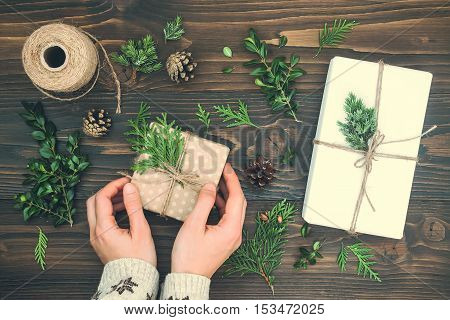 Girl wrapping christmas gift. Woman's hands holding decorated gift box on rustic wooden table. Christmas or New year DIY packing. Overhead flat lay top view