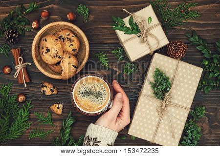 Opening Christmas present. Woman's hands holding a cup of hot coffee on rustic wooden table. Ideal Christmas morning. Overhead flat lay top view