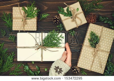Opening Christmas present. Woman's hands holding decorated gift box on rustic wooden table. Christmas or New year DIY packing. Overhead flat lay top view