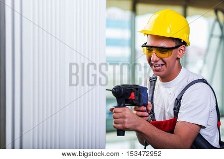 Man drilling the wall with drill perforator