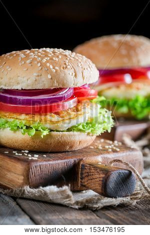 Closeup Of Two Burgers With Vegetables And Fried Egg