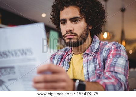 Man reading newspaper in cafeteria
