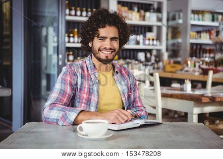 Portrait of man with a diary in cafeteria