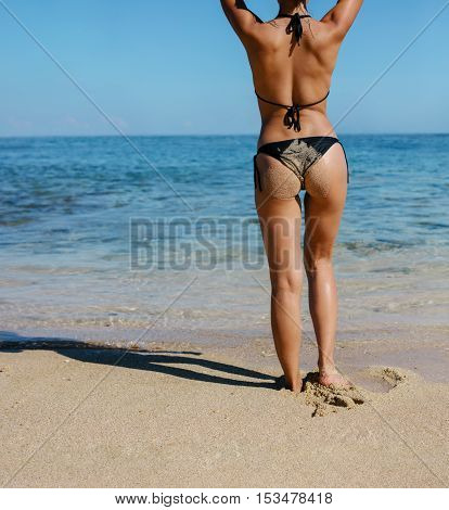 Rear view of female model in bikini covered with sand standing on the beach. Low section shot of young woman standing on the sea shore.