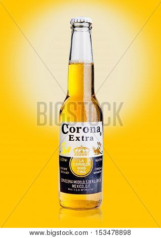 LONDON UNITED KINGDOM - October 23 2016: Bottle of Corona Extra Beer on yellow background. Corona produced by Grupo Modelo with Anheuser Busch InBev is the most popular imported beer in the US.