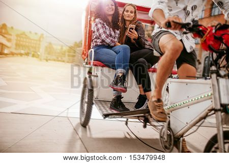 Young women sitting on tricycle and posing for selfie. Female friends enjoying tricycle ride on road and taking self portrait with mobile phone.