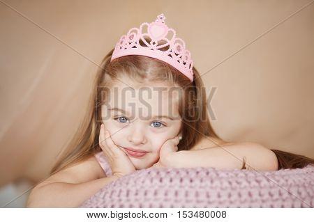 Portrait of beautiful princess girl in pink dress lying down bored.
