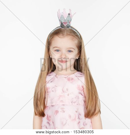 Square portrait of cute smiling little blond girl in princess dress wearing a crown isolated on white. Long hairstyle