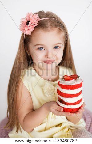 Little kid blonde girl holding a red velvet cake sitting isolated on white background. Birthday concept