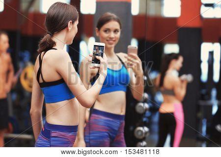 Young sportive woman taking selfie near mirror in gym