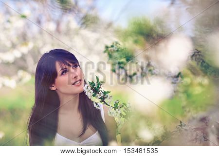 Portrait of young romantic woman outdoors relaxing dreaming in blooming trees in spring. Toned image