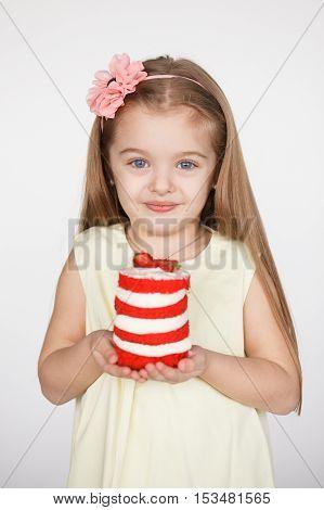 Little kid blonde girl holding a red velvet cake isolated on white background. Birthday concept
