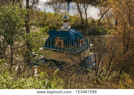 Autumn landscape chapel in the forest among trees rivers plunge pool