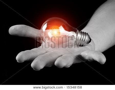 Hand holding light bulb isolated on black
