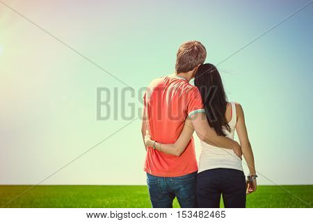 Back view of young relaxed couple hug and look into the distance outdoors. Toned image