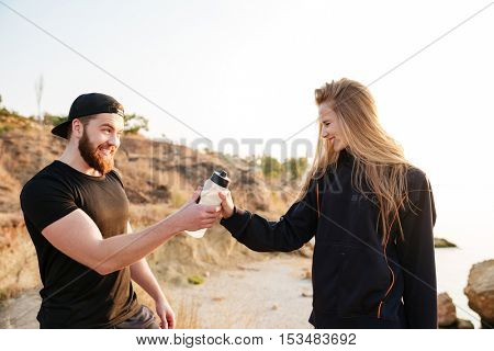 Cheerful healthy couple resting together with bottle of water outdoors at the beach