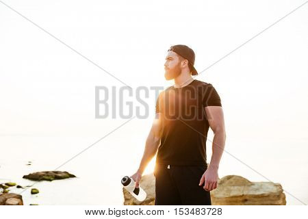 Handsome young sportsman standing and holding water bottle outdoors