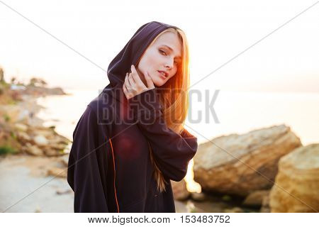 Beautiful young fitness woman in hoodie standing at the beach and looking at camera