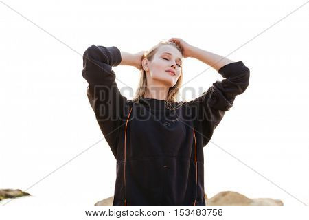 Young attractive sports woman in hoodie resting after training on beach