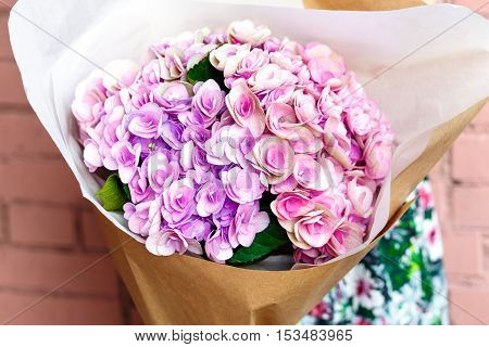 woman with bouquet of pink flowers in kraft paper on background of a brick wall