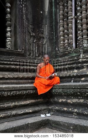 SIEM REAP CAMBODIA - OCT 20 2016: Monk meditates at the Angkor Wat temple in Siem Reap Cambodia.