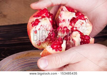 Hands break a pomegranate on wood board. Food background