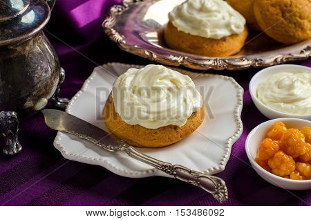 Cream cake on a white saucer. A vintage knife. Cloudberries and cream in bowls. Still life with vintage silver utensils. Purple background.