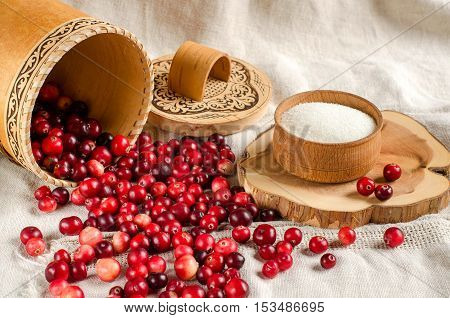 Cranberries are poured from a basket. The red berries. Sugar in a wooden bowl. A bright background. Place for text.