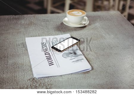Mobile phone with newspaper and coffee cup on a table in cafeteria