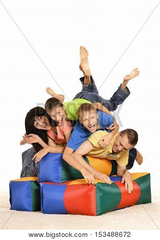 Family playing with colored cushions on a white background