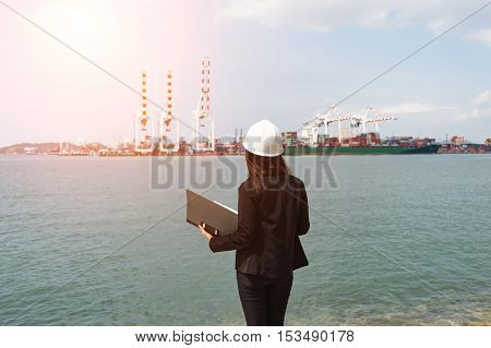 The engineer working with container Cargo freight ship in shipyard at dusk for Logistic Import Export background