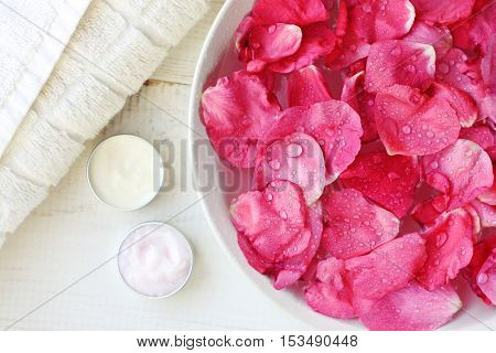 Aroma spa skincare treatment. Rose petals in bowl, body care moisturizers, white towel. Pampering beauty routine.