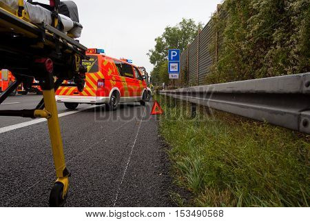 HANNOVER / GERMANY - OCTOBER 25 2016: Emergency stretcher stands with a german firefighting truck on freeway a2 by a truck crash near Hannover.