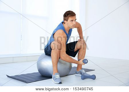 Young man doing exercises with dumb-bells and ball on rug