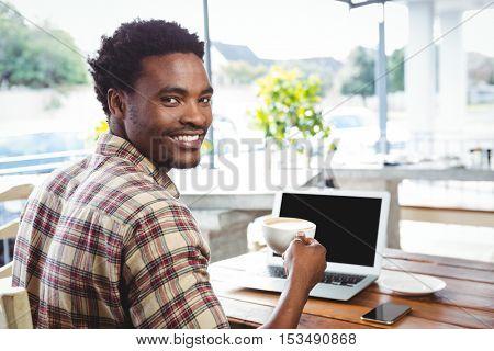 Happy man having coffee in cafeteria
