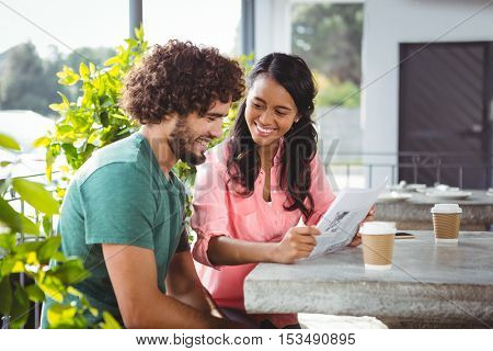 Couple holding menu card in cafeteria