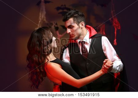 Young people dressed as vampires for Halloween party, on dark background