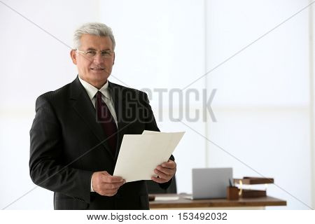 Portrait of successful mature businessman with papers in office