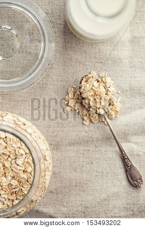 Dry rolled oatmeal in silver spoon. Top view.