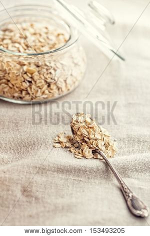 Dry rolled oatmeal in silver spoon.