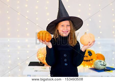 Teenager girl in witch costume posing with pumpkins and bottle of blue potion during Halloween party