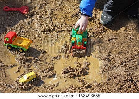 Part of the image of a small child who sits in the wet sand and plays with a toy construction machine. Visible hand dressed in a blue jacket.