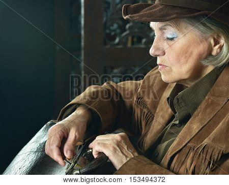 Mature female Bandit with gun in the wild west