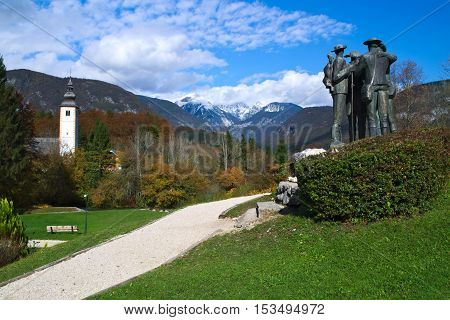 Statue dedicated to the first four men  who climb the Triglav mountain next the Church of St. John the Baptist at Lake Bohinj (Bohinjsko jezero), Slovenia
