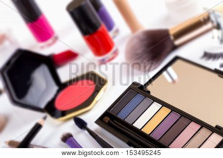 cosmetics on the table - focus on eyeshadows palette