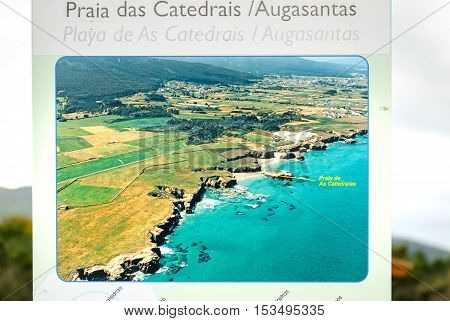 A Coruna Spain - May 29 2016: Turist sign and map of Cathedrals beach (playa de las catedrales) Spain Atlantic ocean. Famous beach in Northern Spain. Natural rock arch on Cathedrals beach in low tide (Cantabric coast Lugo (Galicia) Spain).